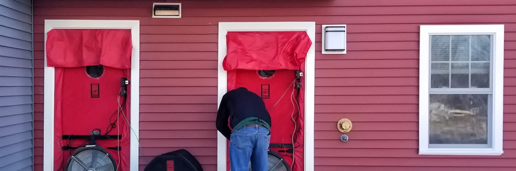 Worker performing Infiltration Testing on residential home