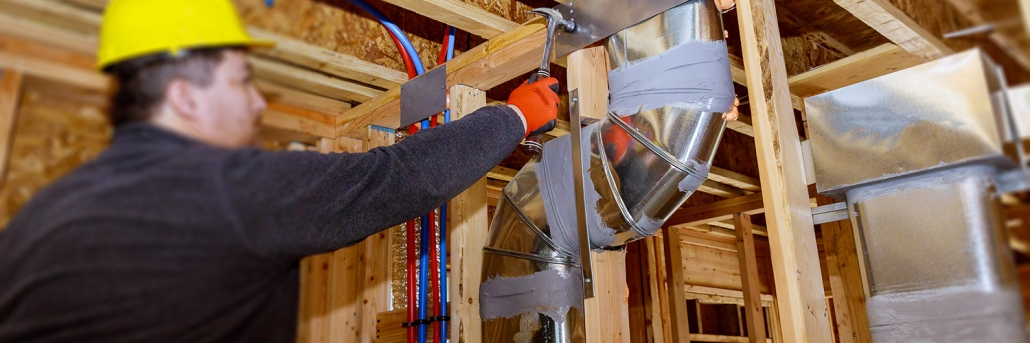 Worker performing air duct testing services on new house construction